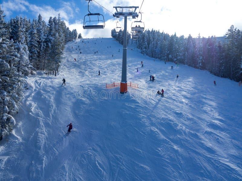 Cabina del teleférico en picos de montaña de Bansko, de Bulgaria y de la nieve en el fondo Cielo azul, 2017 foto de archivo