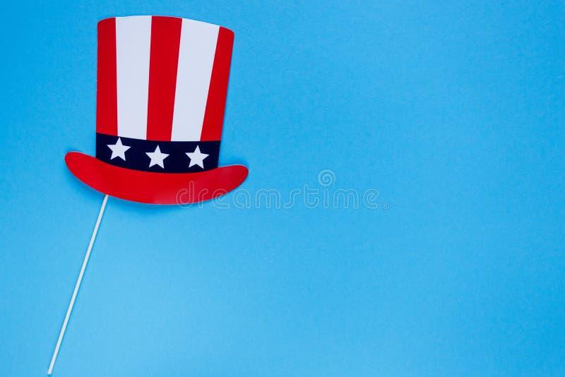 Cabina della foto per il quarto luglio Cappello sui bastoni su fondo blu Colori della bandiera americana Festa dell'indipendenza, fotografia stock