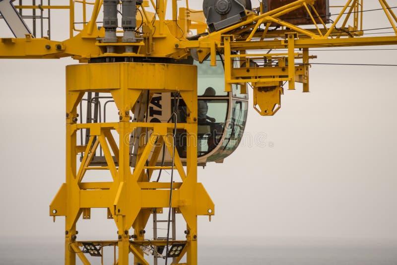 Cabina della gru a torre della costruzione con il livello dell'operatore sopra l'oceano fotografia stock