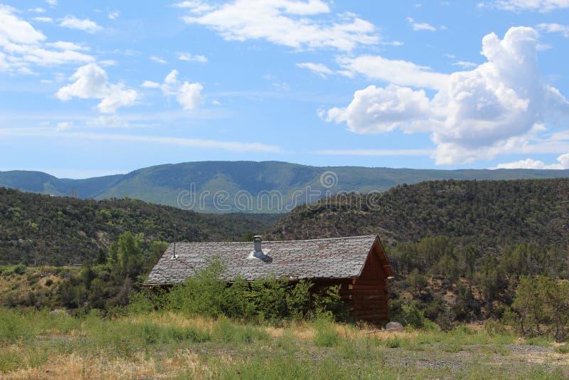 Cabina di ceppo sul fianco di una montagna fotografia stock libera da diritti