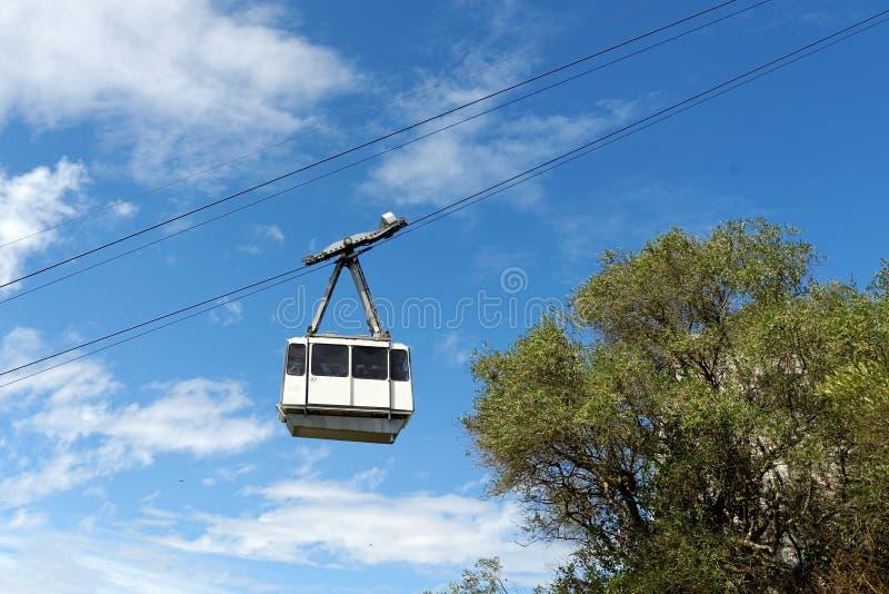 Cabina di funivia bianca contro il cielo blu fotografia stock libera da diritti