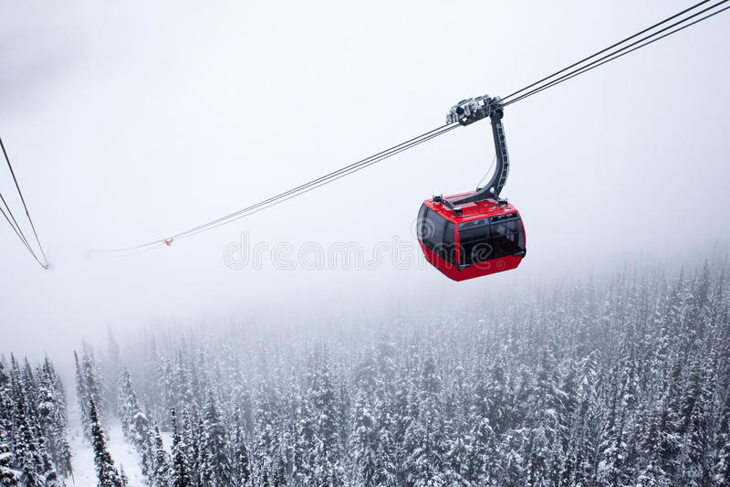 Cabina di funivia rossa nebbiosa fotografie stock