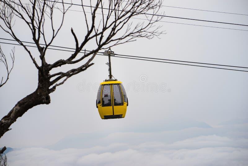 Cabina di funivia sopra le nuvole ed albero asciutto su fondo fotografie stock libere da diritti