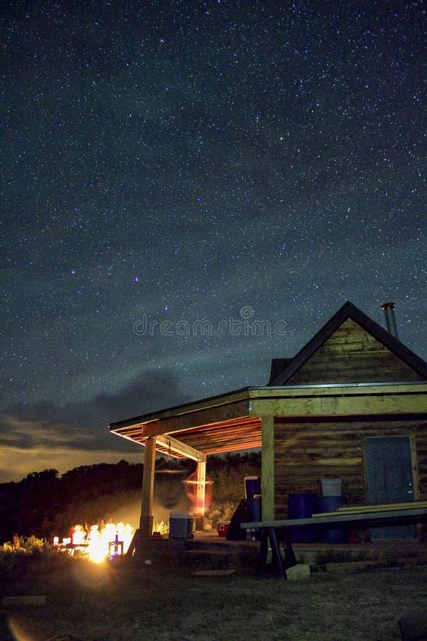Cabina e fuoco di accampamento sotto le stelle fotografie stock