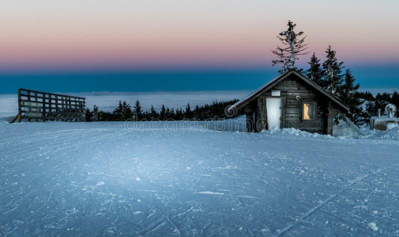 Cabina en las montañas en invierno fotos de archivo