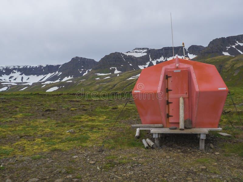 Cabina roja del refugio de la emergencia en el sitio para acampar del hloduvik que se coloca en fotos de archivo libres de regalías
