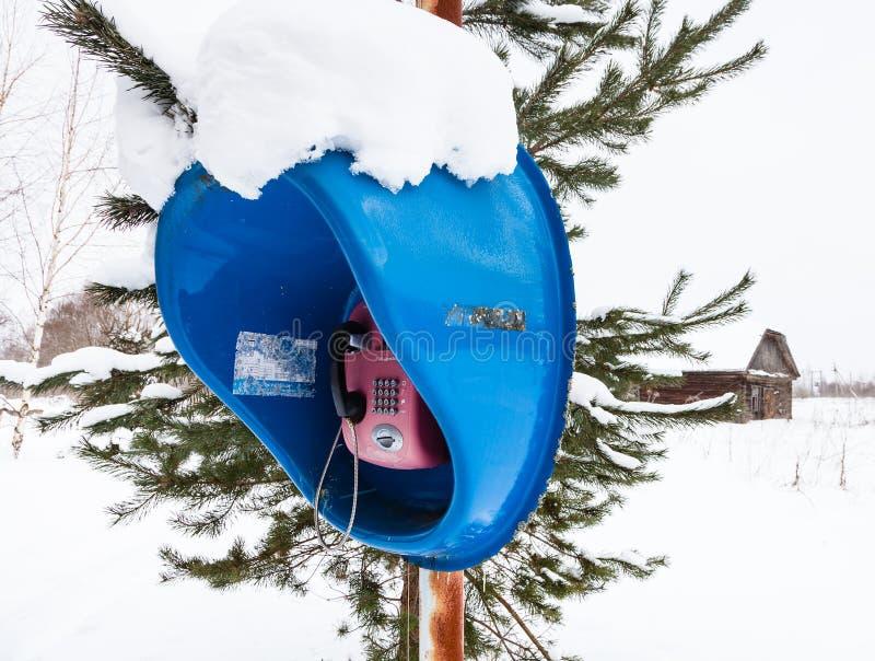 Cabina telefonica all'aperto nel campo di neve in villaggio fotografia stock