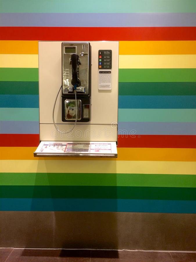 Cabina telefonica pubblica su una parete colorata arcobaleno all'aeroporto di Changi a Singapore fotografia stock libera da diritti