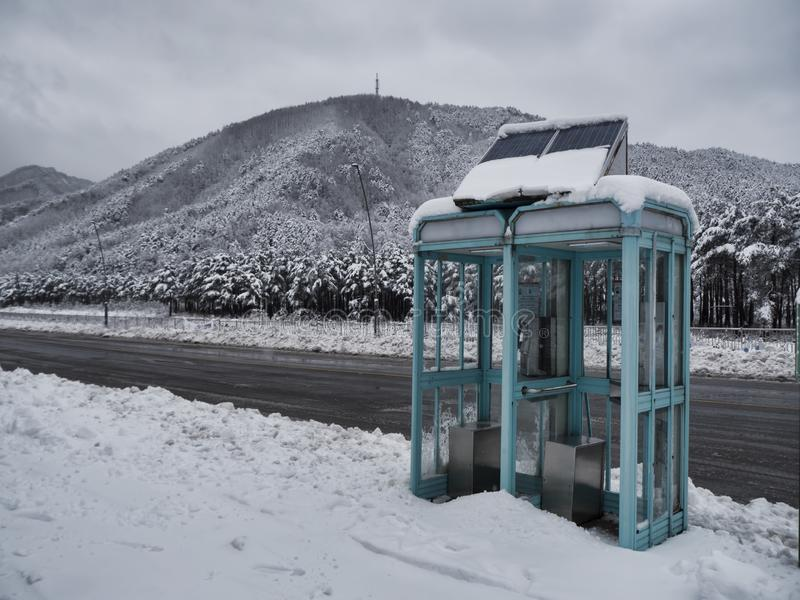 Cabina telefonica su una strada innevata della montagna immagini stock libere da diritti