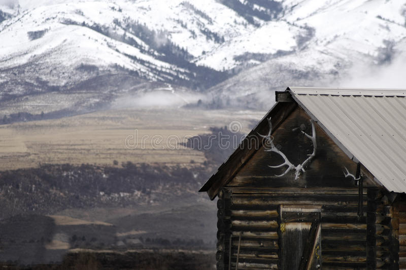 Cabina vieja con las montañas de la nieve y las astas de los alces foto de archivo