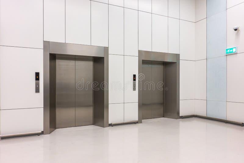 cabinas de acero modernas del elevador con las puertas cerradas en el pasillo del negocio fotos de archivo libres de regalías