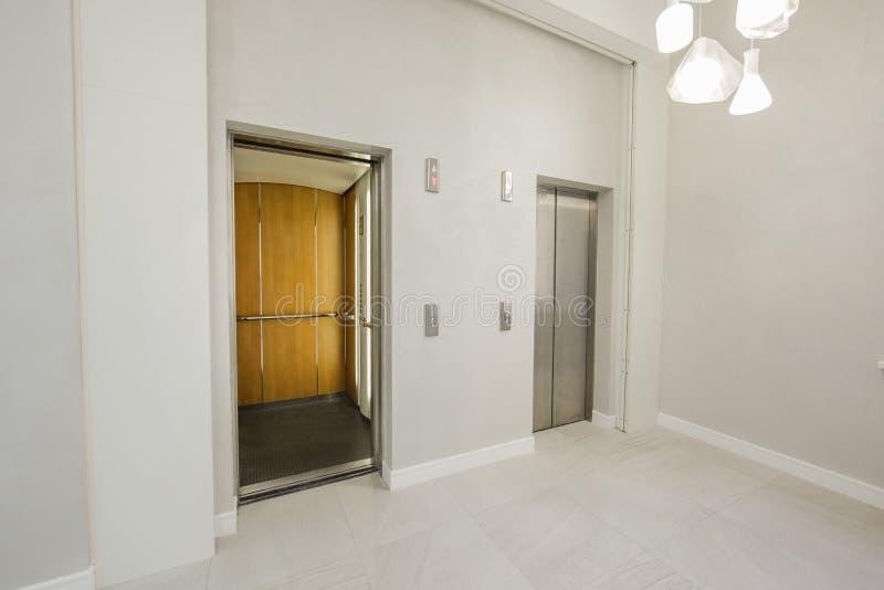 Cabinas de acero modernas del elevador en el salón o el hotel, tienda, salón, oficina del negocio, con pantalla grande en perspec imagen de archivo