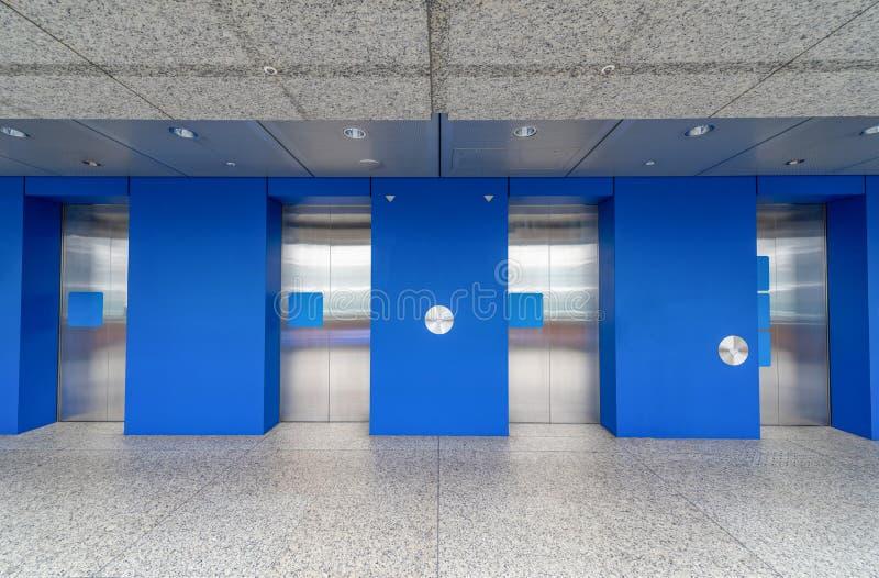 Cabinas de acero modernas del elevador en un edificio del hotel del pasillo o de oficinas fotos de archivo