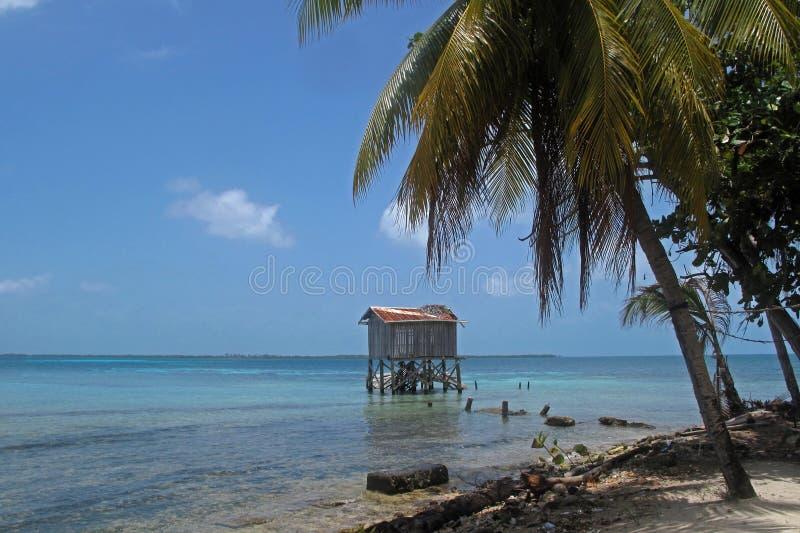 Cabinas en los zancos en la pequeña isla del tabaco Caye, Belice imágenes de archivo libres de regalías