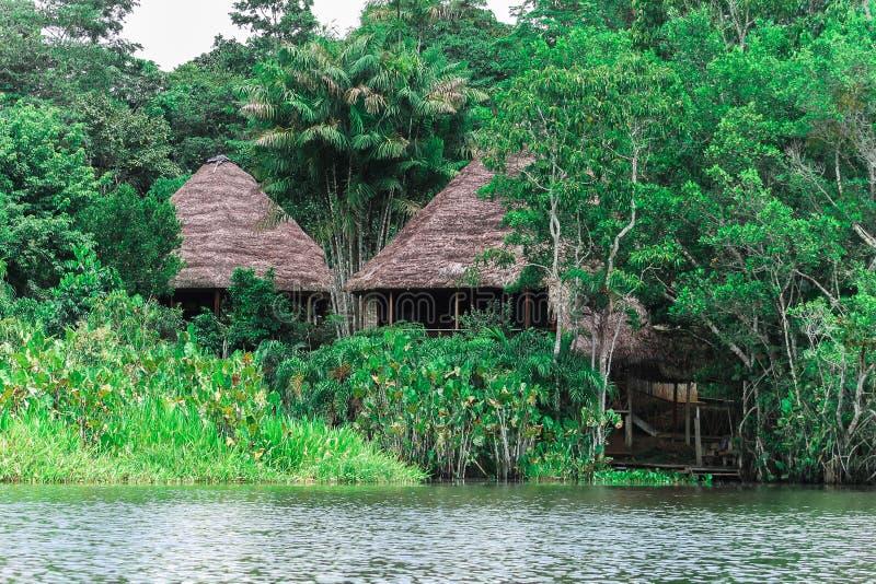 Cabinas a lo largo del río en el Amazonas fotos de archivo