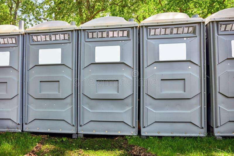 Cabinas m?viles reforzadas fibra de vidrio del toilette del pol?mero en un parque foto de archivo libre de regalías