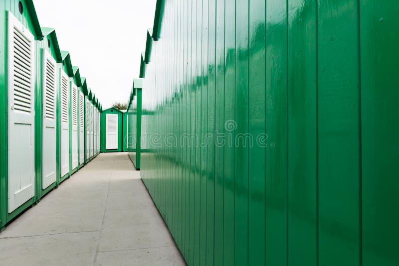 Cabinas pintadas verde de la playa con las puertas blancas fotografía de archivo libre de regalías