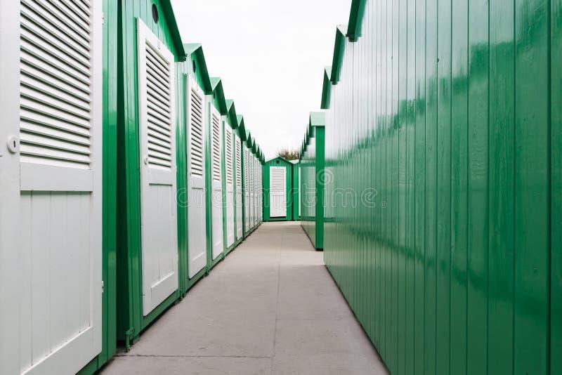 Cabinas pintadas verde de la playa con las puertas blancas fotografía de archivo