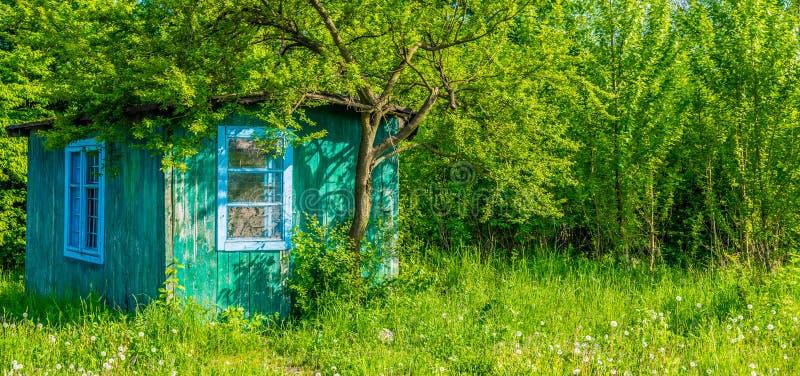 Cabine abandonada em um gramado verde fotos de stock
