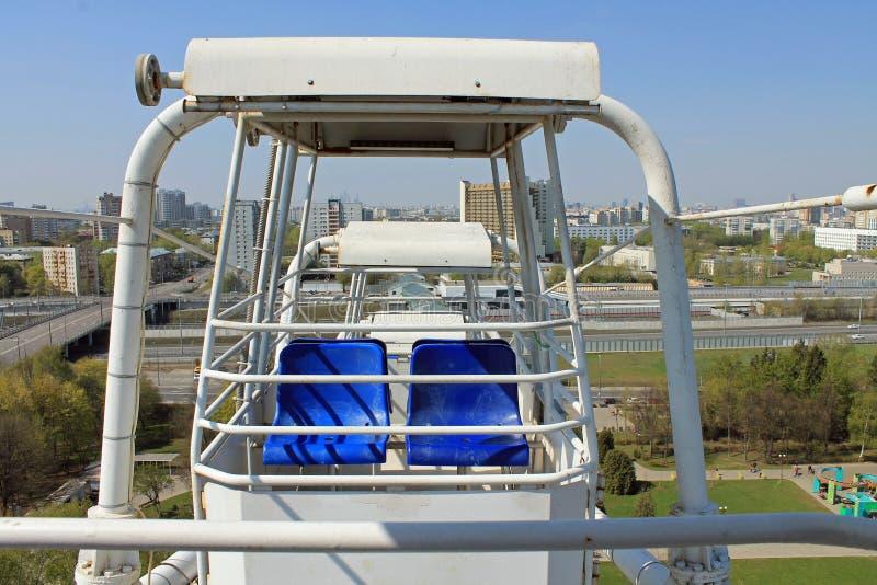 Cabine blanche vide ouverte de la grande roue au-dessus de la ville contre le ciel bleu photo libre de droits