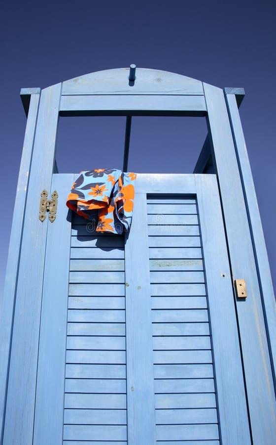 Cabine bleue de robe à la plage avec un procès de natation traînant photo stock