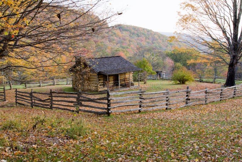 Cabine de registro do outono com cerca de trilho fotos de stock royalty free