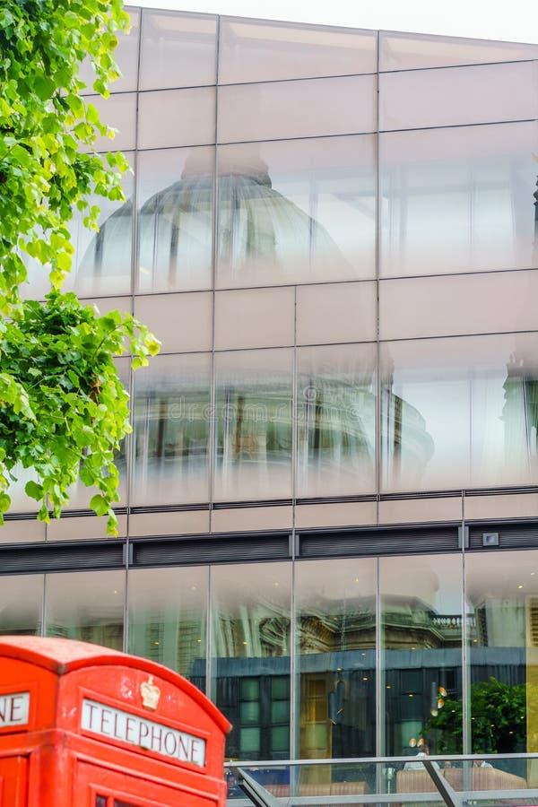 Cabine de telefone vermelha com reflexão da catedral do ` s de St Paul em Londres fotografia de stock