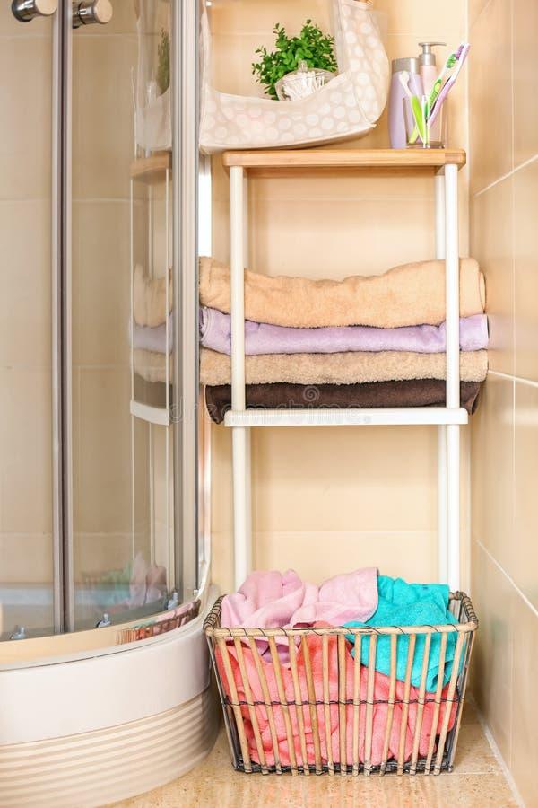 Cabine do chuveiro, prateleiras com toalhas limpas e cesta de lavanderia no banheiro foto de stock