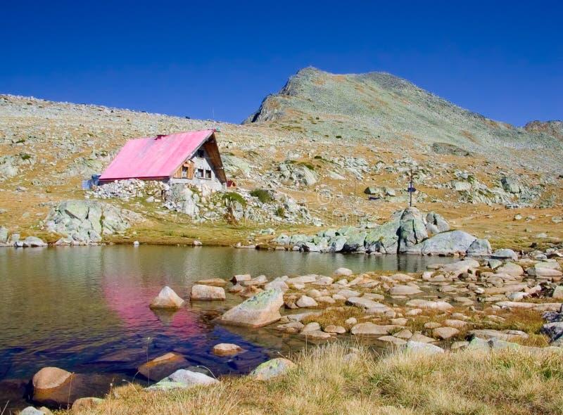 Cabine en een ijzig meer omhoog in nationaal park Pirin, Bulgarije stock fotografie