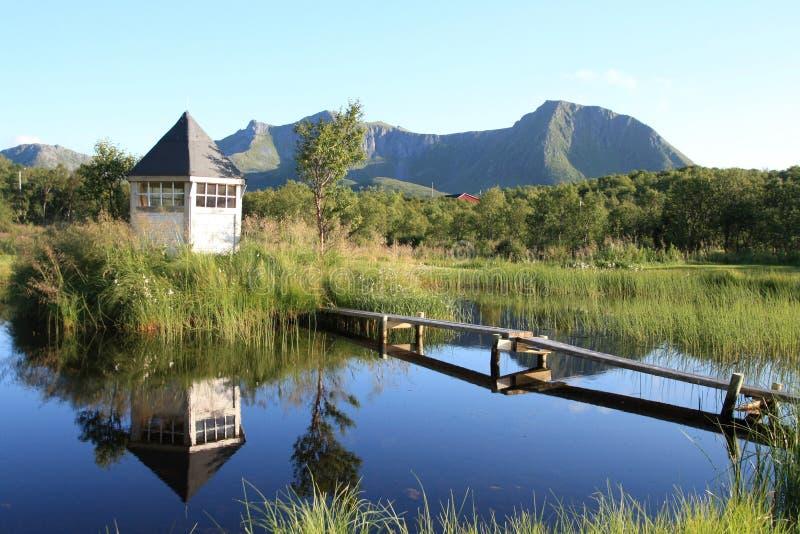 Cabine et supports reflétant dans le lac Lofoten image libre de droits