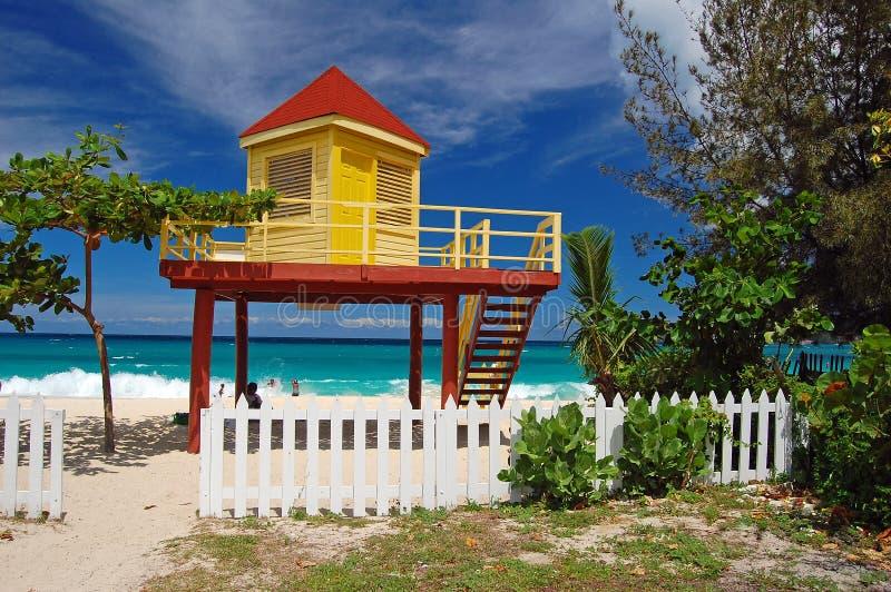 Cabine jaune et rouge de maître nageur sur la plage grande d'Anse photographie stock libre de droits