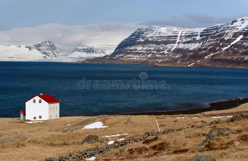 Cabine perto do lago e das montanhas snowcapped do islandês dos westfjords foto de stock royalty free