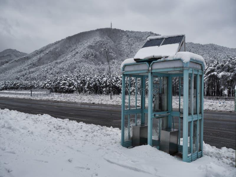 Cabine téléphonique sur une route couverte de neige de montagne images libres de droits