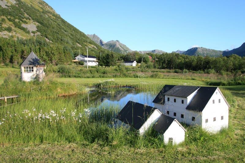 Cabines et maisons reflétant dans le lac Lofoten photo stock