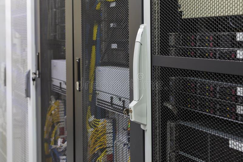 Cabinet au centre de traitement des données avec des ordinateurs serveur, commutateurs, routeurs, câbles sous clef photo libre de droits