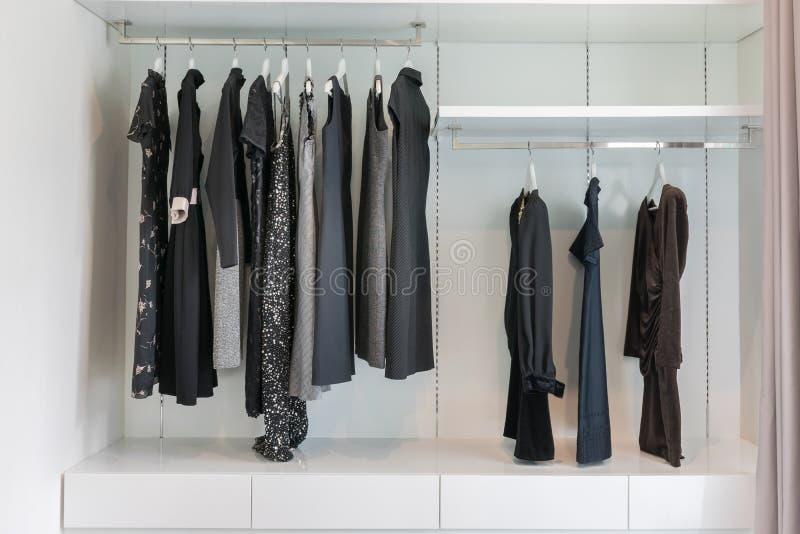 Cabinet avec la rangée de la robe noire accrochant sur le cintre de manteau image libre de droits