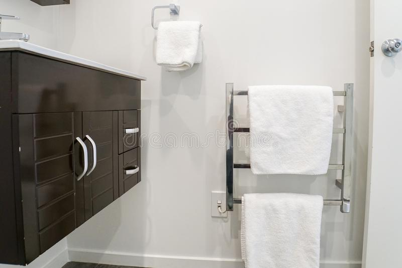Cabinet at basin and white towel on metal rails for taking a bath royalty free stock photo