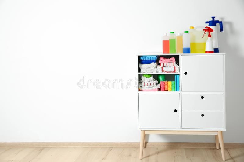 Cabinet With Different Cleaning Supplies Near White Wall Stock