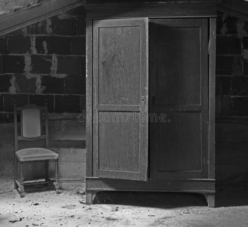 Cabinet effrayant dans le grenier poussiéreux avec une chaise le long photos stock