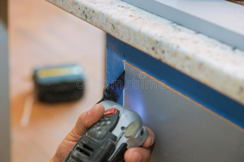 Cabinet furniture, cutting oscillating multi-function power tool on kitchen cabinets framing. Furniture cutting oscillating multi function power tool on kitchen royalty free stock photography