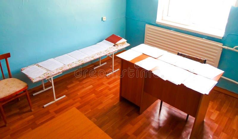 Cabinet médical à l'école avec une table de placard et un lavabo murs bleus et blancs, robes médicales sur le cintre photographie stock libre de droits