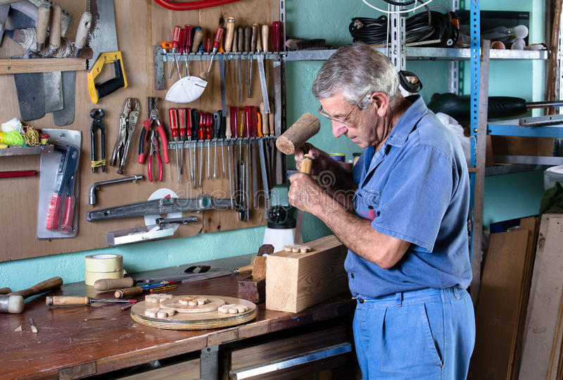 Cabinetmaker carving wood with a chisel and hammer in workbench royalty free stock image
