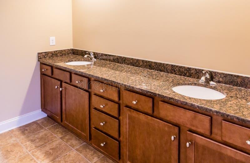 Cabinets de salle de bains avec la vanité de granit et le plancher de tuiles photos libres de droits