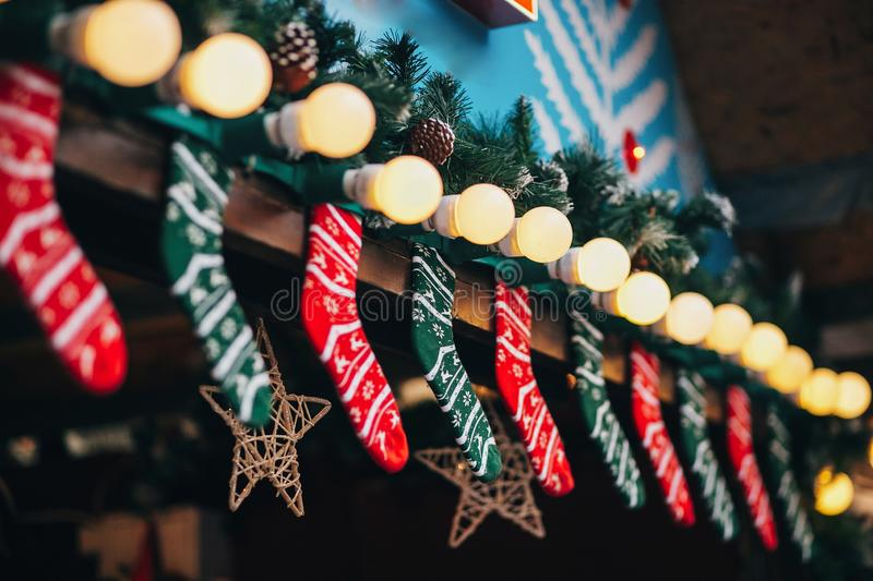 Cabins with stylish christmas decorations on european city market. Holiday socks and stockings, garland lights and fir branches o stock images
