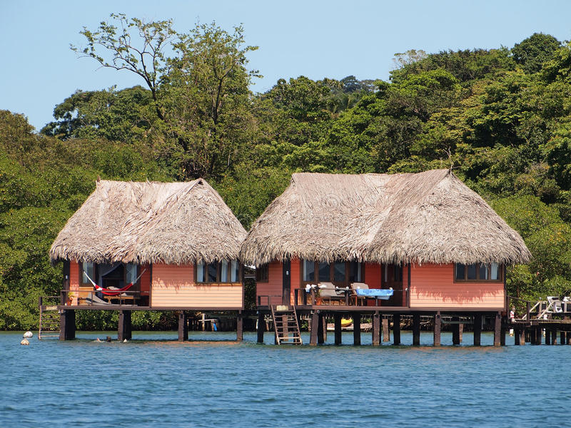 Cabins with thatched roof over the water royalty free stock photo