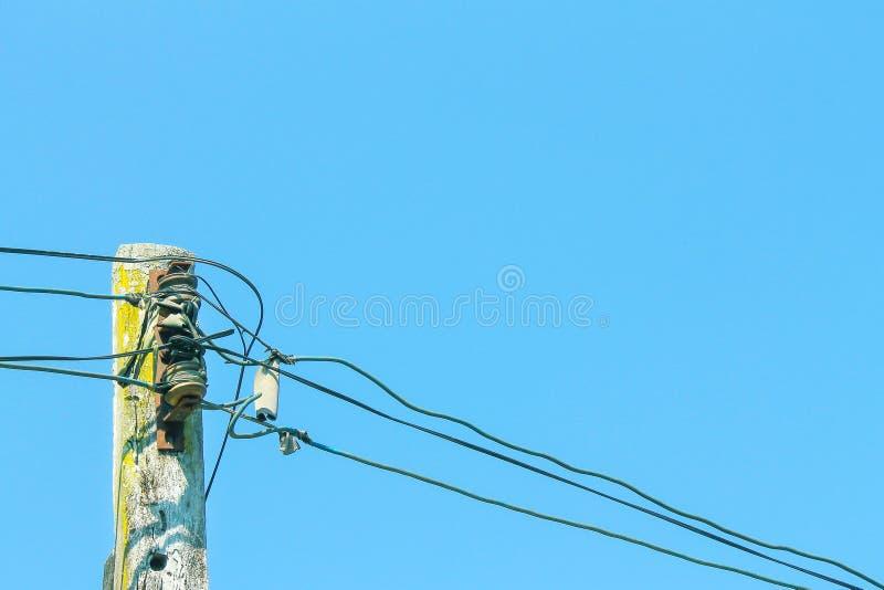 Cable électrique de basse tension sur le vieux poteau en bois et le fond clair de ciel bleu photo libre de droits