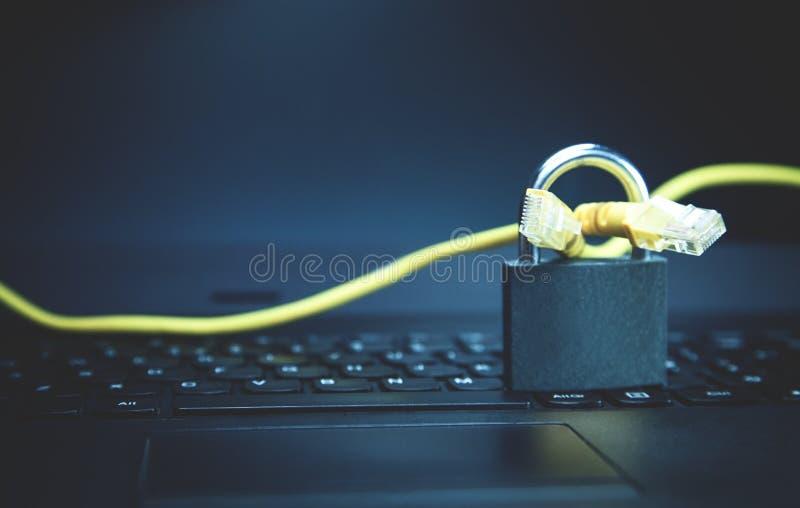 Cable amarillo de la red con un candado en el ordenador portátil Seguridad del web fotografía de archivo libre de regalías