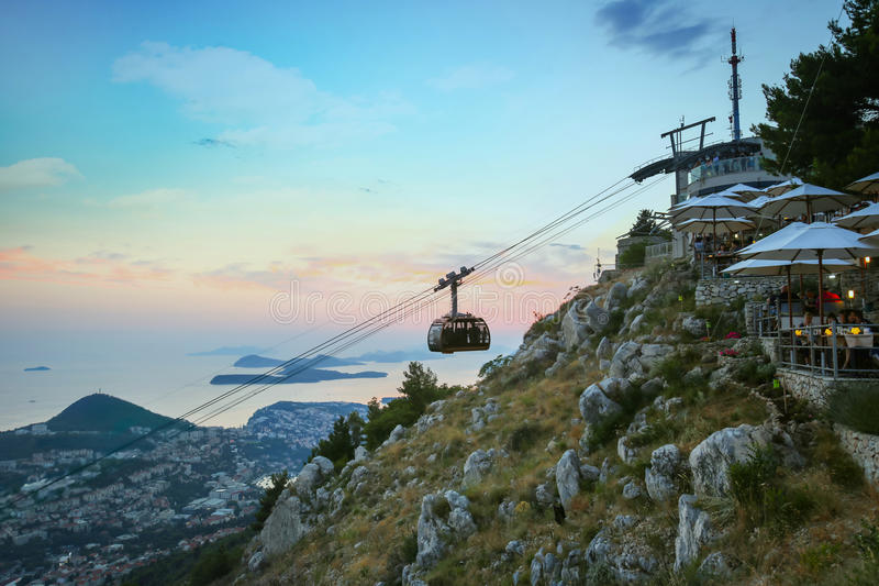 Cable car above Dubrovnik. DUBROVNIK, CROATIA - JULY 20, 2017 : Srd hill, a mountain behind the ancient old town Dubrovnik with cable car and restaurant in stock image