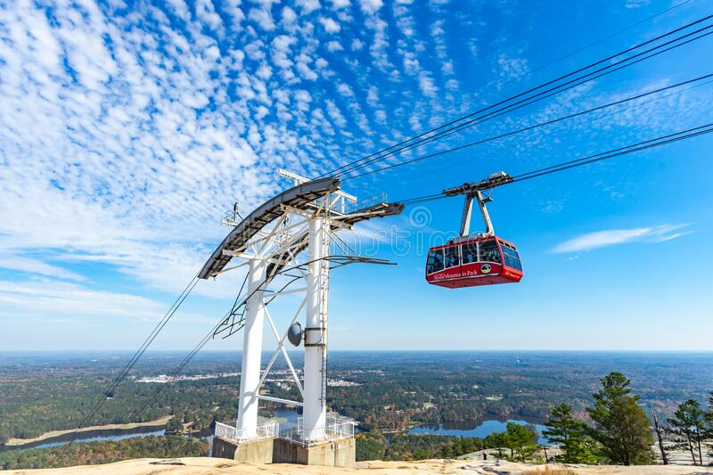 A cable car or gondola passing above stone mountain park. Stone Mountain, Georgia / United States - October 2018 : Skyride, a cable car or gondola riding above royalty free stock images