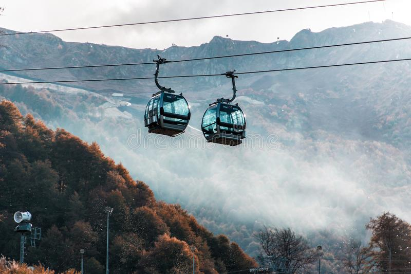 Cable car on Krasnaya Polyana in Sochi. Very in the mountains.  turquoise and orange.  stunning scenery. mountains in clouds royalty free stock photos